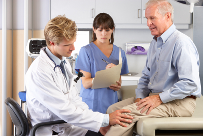 doctor checking the knee of a senior